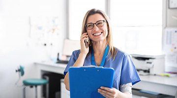 dental assistant talking on the phone and holding blue clipboard