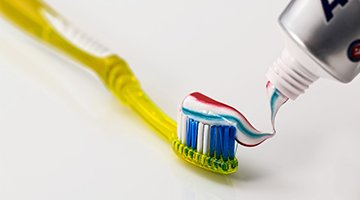 toothpaste on yellow toothbrush
