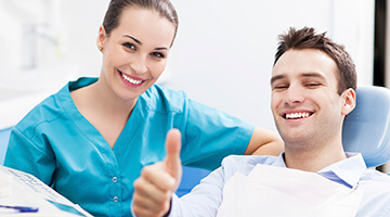 Male patient giving thumbs up next to dentist