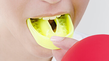 Patient putting on her mouthguard