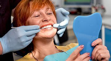 Orange Park Restorative Dentistry Woman viewing her smile in mirror