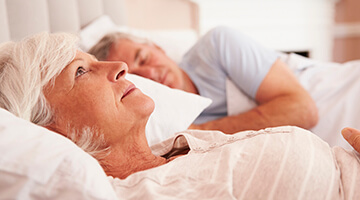 Elderly woman annoyed by snoring husband