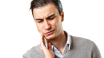 Man in sweater holding jaw in pain