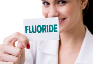 "Smiling dentist holding note saying ""fluoride"""