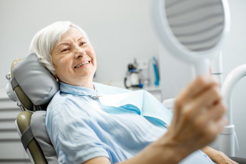 Senior woman smiling at reflection in dentist's office