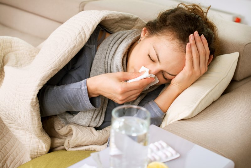 Woman with seasonal allergies laying on a couch