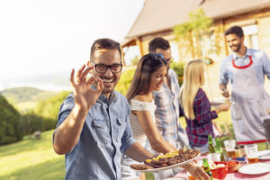 Man smiling at backyard cookout with friends
